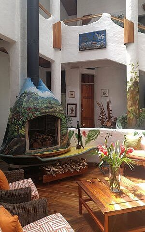 Artistic hotel lobby with painted fireplace at Finca Rosa Blanca luxury hotel in Costa Rica